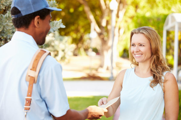 Mailman Delivering Mail to Smiling Woman - Mailing Methods